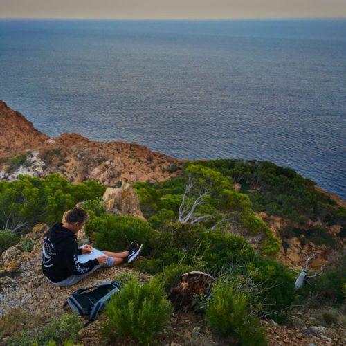 Christophe Monteil dessinant sur les falaises de Sa Tuna, en Catalogne (Espagne)